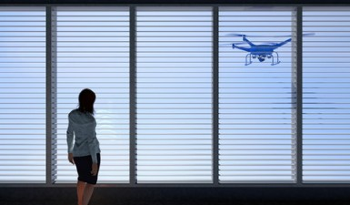 3D render of a UAV drone peering through a window with horizontal blinds as a female human figure looks on. Fictitious UAV is a unique design. Motion blur and lens flare for dramatic effect.